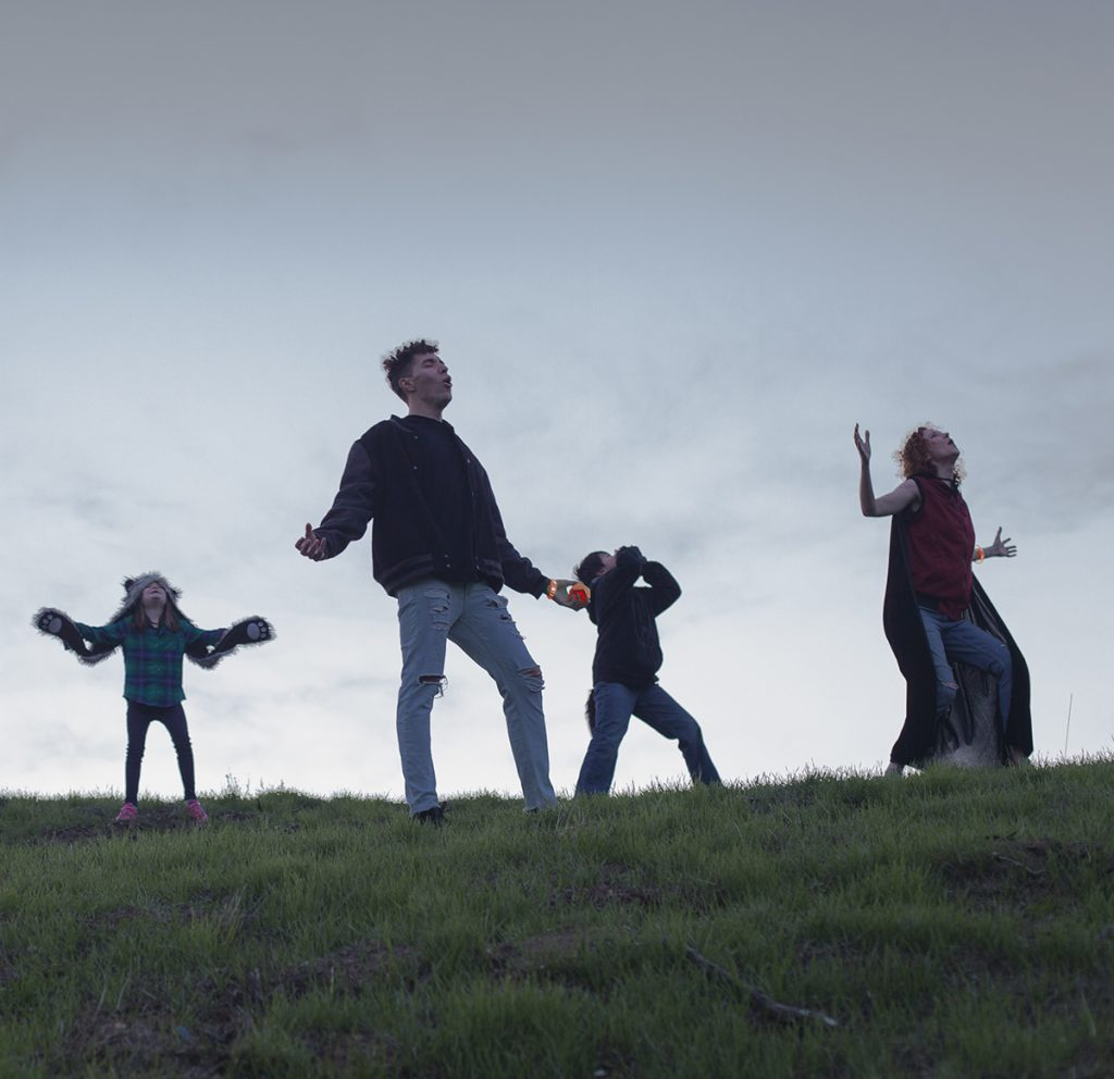 Four teens howl at the moon while standing on a grassy hill playing Wizards & Werewolves.