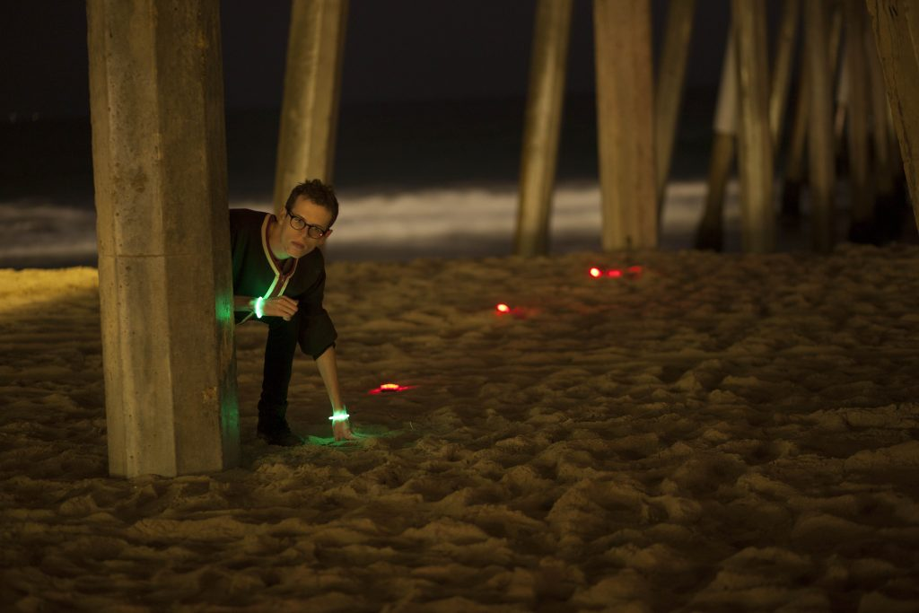 A boy plays glow in the dark Capture the Flag on a beach.
