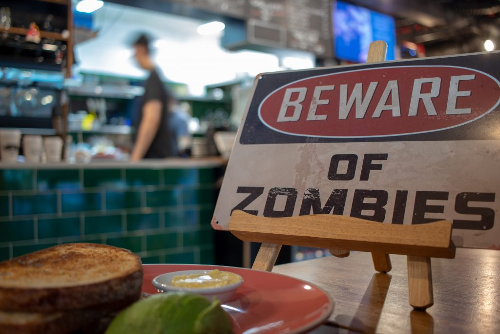 "A sign on a table at a restaurant reads ""BEWARE OF ZOMBIES."""