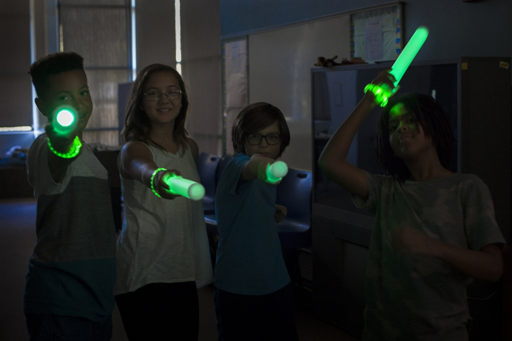 Four kids point glow swords from Glow Battle at the camera.