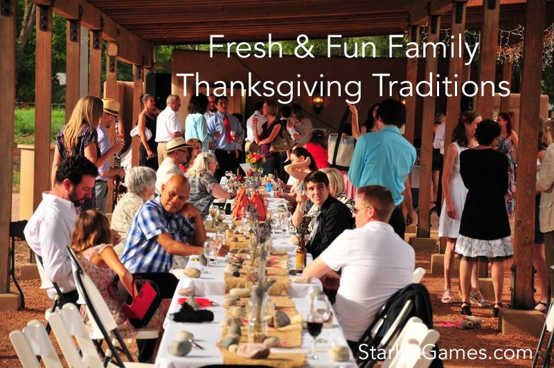 A family sits around a large table enjoying a Thanksgiving dinner.