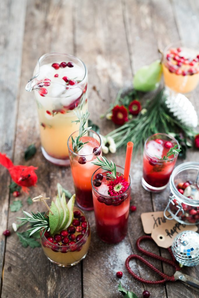 Holiday drinks and mistletoe sit on a wooden table.