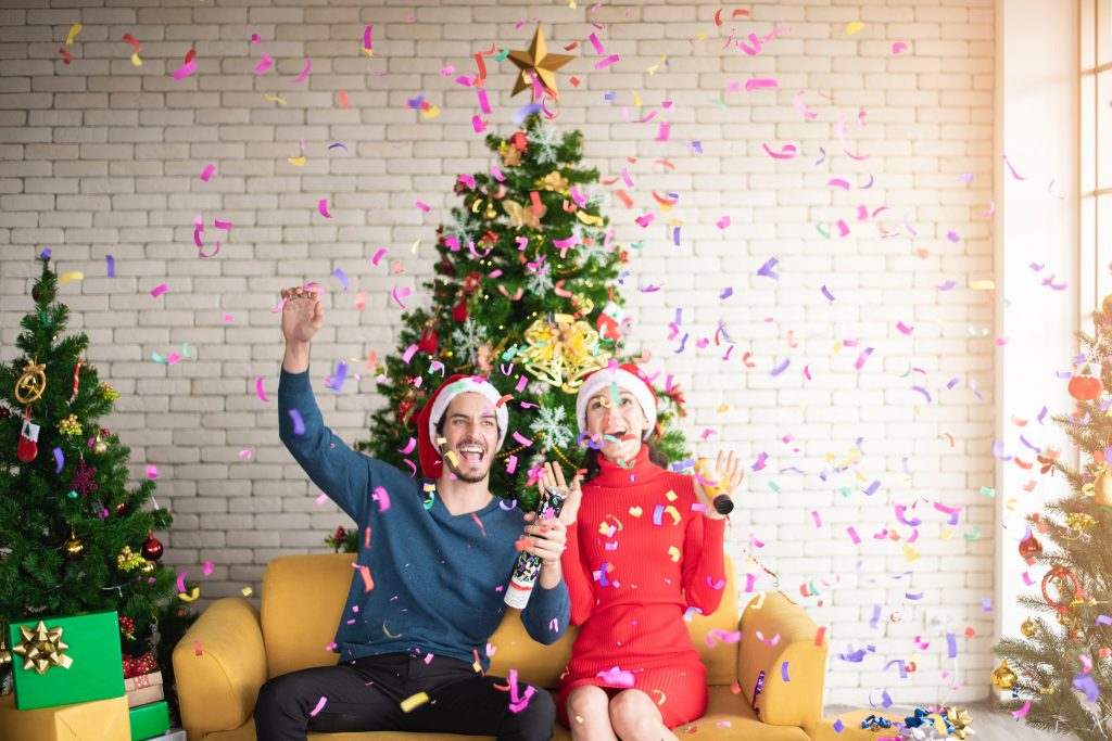 A couple wearing santa hats are smiling and have their hands in the air as confetti falls in their home.