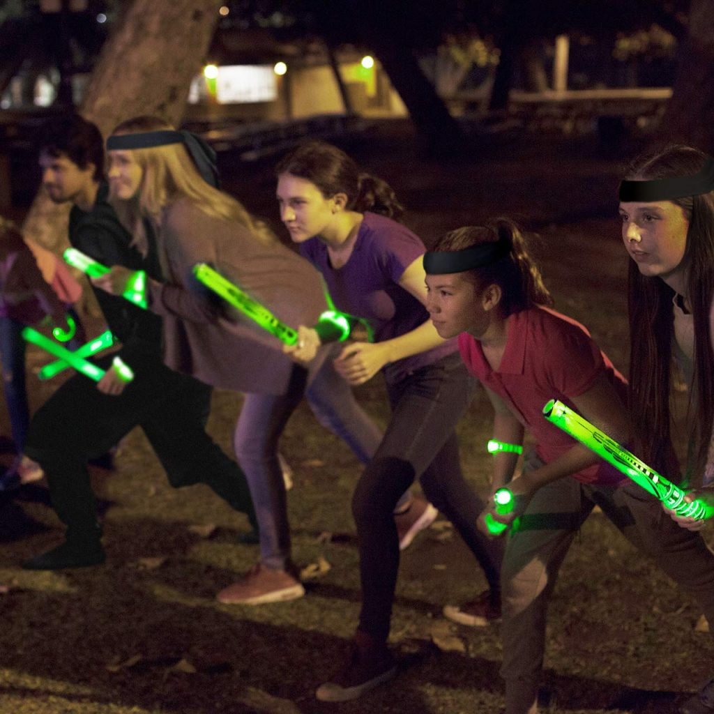 Five kids stand ready for action as they hold glow batons.