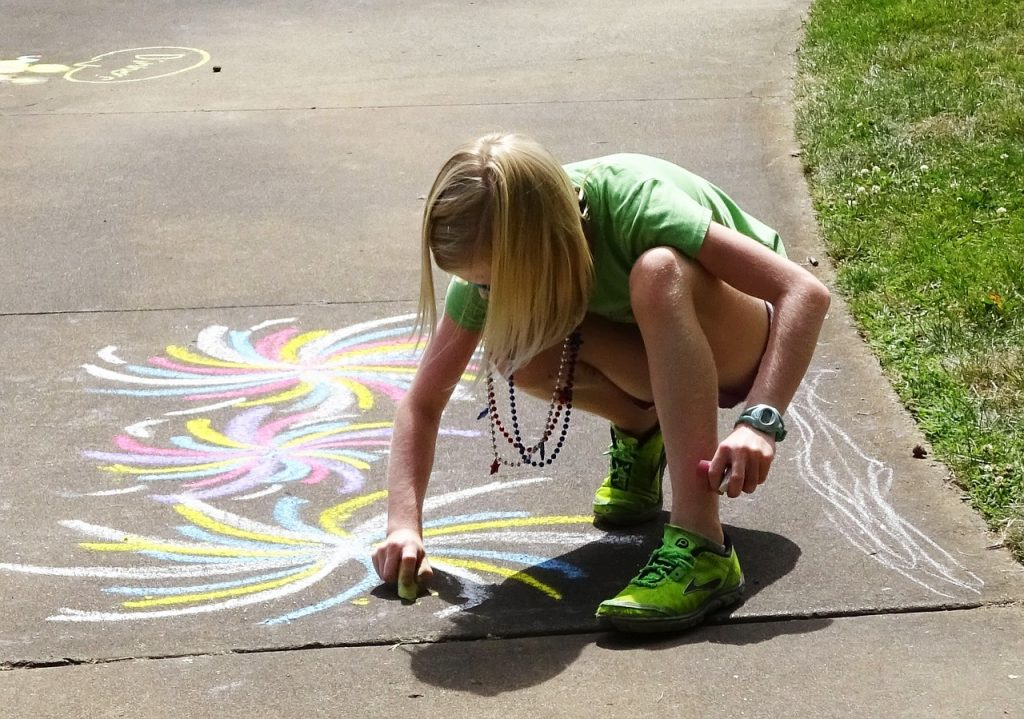 A preteen uses chalk to draw on the sidewalk.