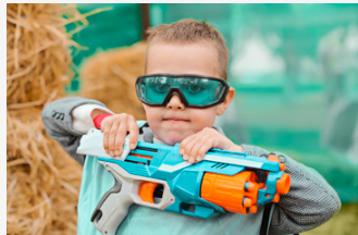 A young boy wearing goggles holds a nerf gun with both hands.