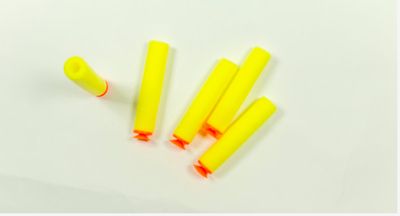 Five yellow nerf darts lay against a white background.