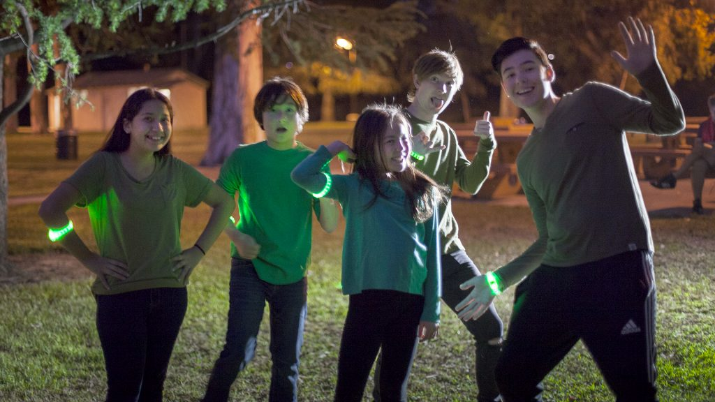 Five kids pose together while wearing green Capture the Flag REDUX bracelets.