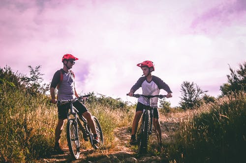 Two preteens ride mountain bikes on a grassy hill.