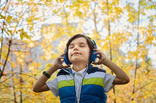 A young boy with headphones closes his eyes to listen to music and is surrounded by yellowing leaves on trees.