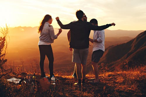 Four teens stand on top of a mountain at sunset.