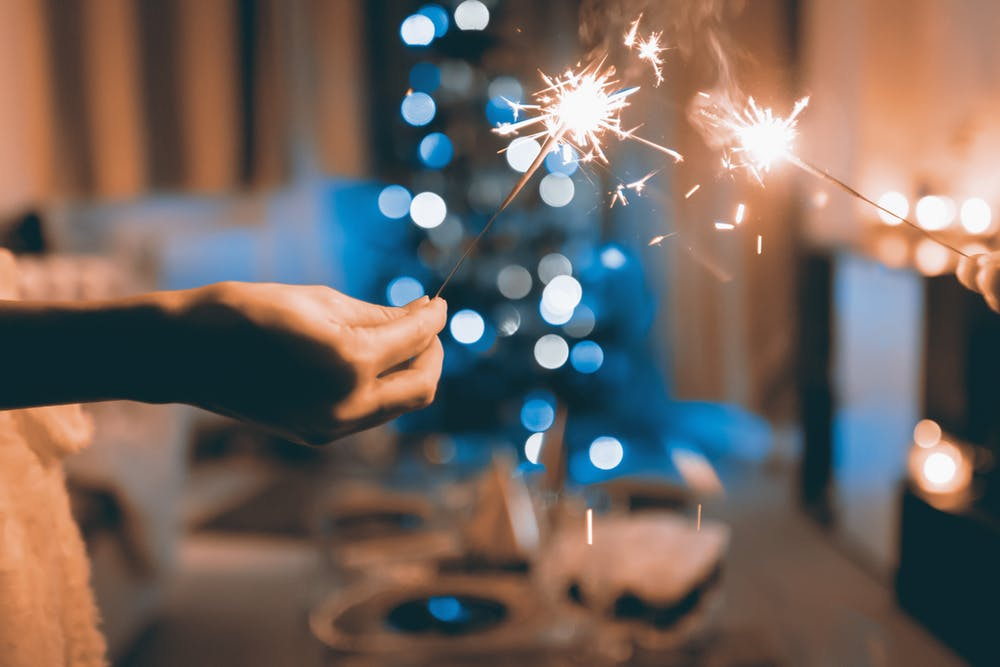 Two hands hold two lit sparklers in a holiday-decorated living room.