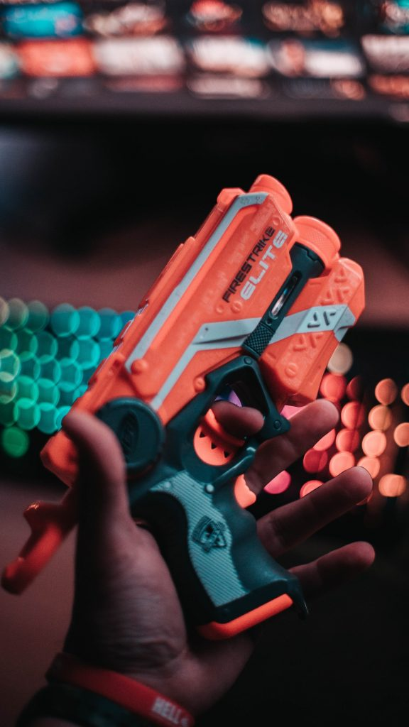 A close up of a hand holding a nerf gun against a blurred background.