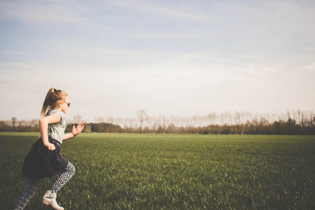 A girl runs through a field