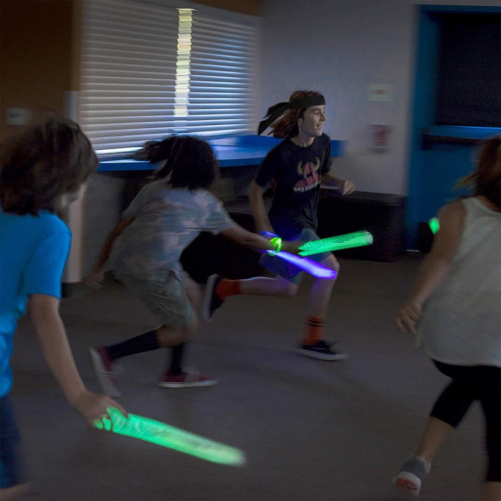 Kids run around a living room with glow batons from their Glow Battle kit.