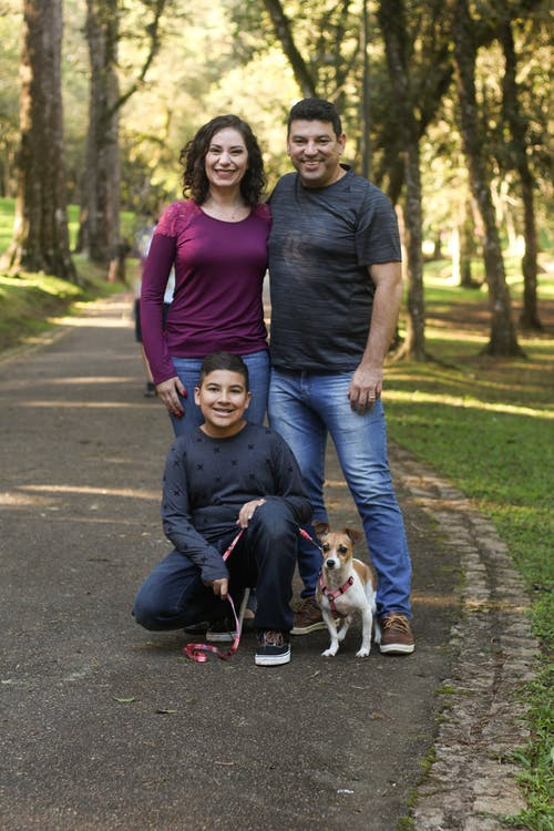 A family of three stands smiling on a path in a forest with their dog.
