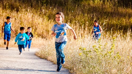 Five boys run happily on a trail through a field.