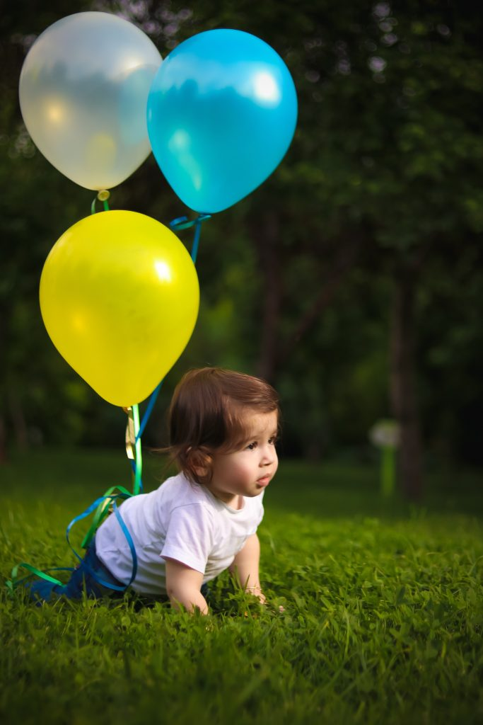 Three balloons are tied to a toddler who crawls on the ground.