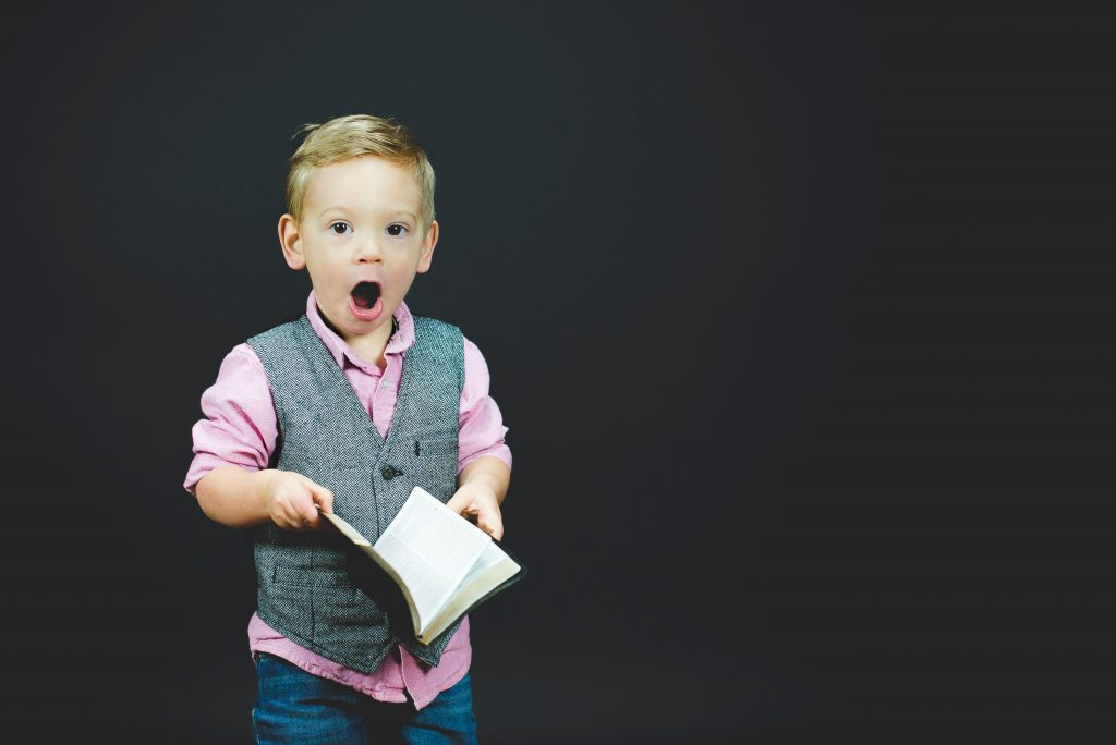 A small boy dressed in business casual wear gasps as he holds a book.