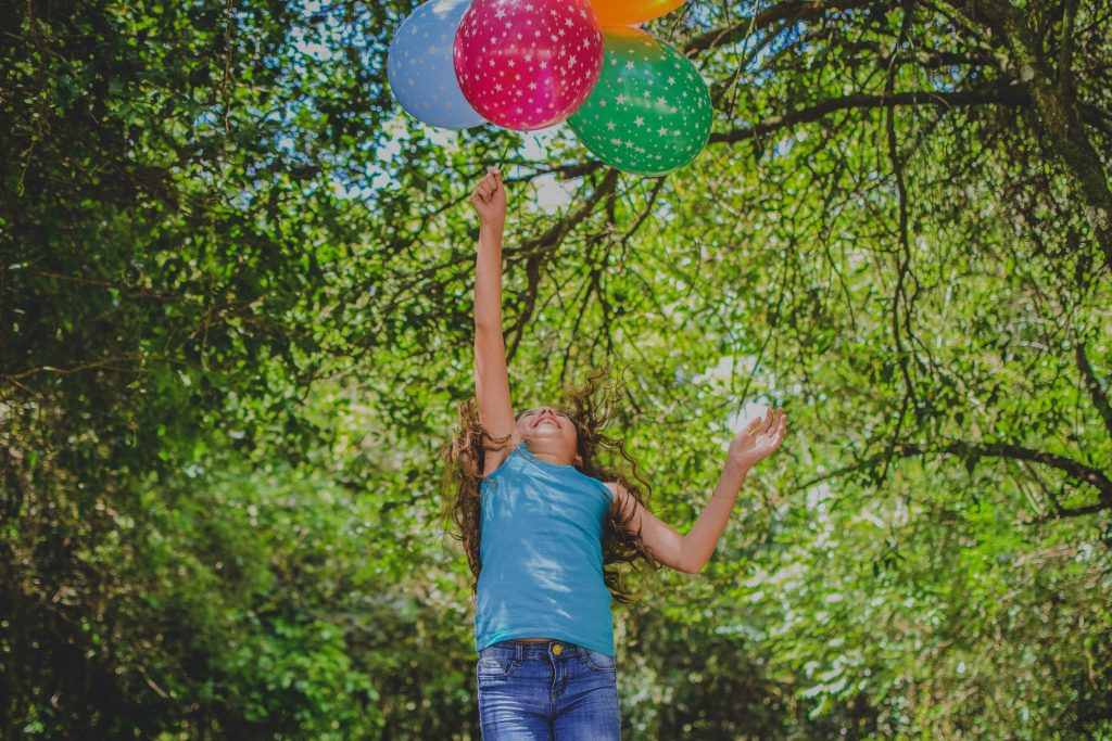 A girl holding four balloons jumps in the air as if they are lifting her off the ground.