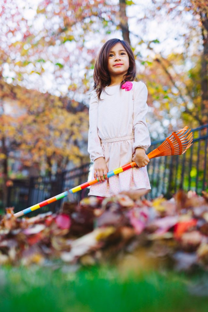A girl rake's leaves in the yard.