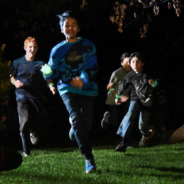 Four kids run through a dark backyard playing Capture the Flag REDUX.