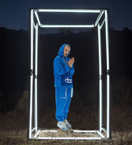 A man stands inside a large, LED outlined box in the middle of a field.